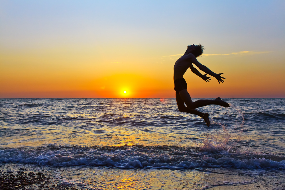 jumping on the beach with sun setting on the horizon