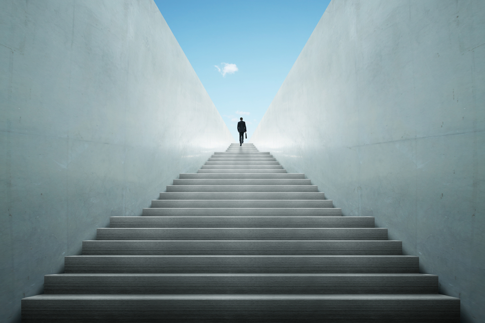 man walking up a staircase undergoing a breakthrough process