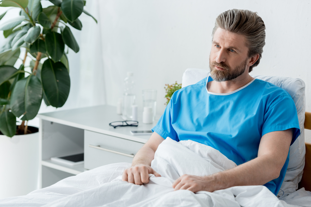 patient in medical gown sitting on bed and looking away in hospital