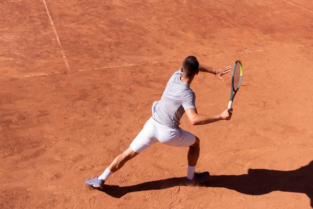 Young male athlete with tennis racket in action