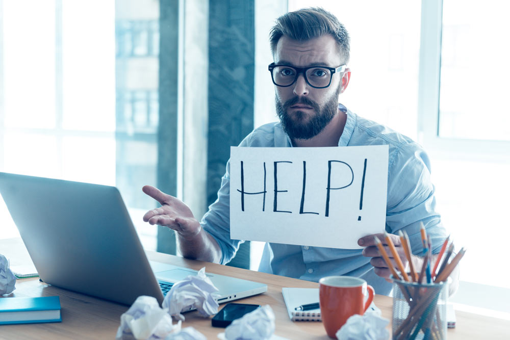 Frustrated man holding piece of paper and asking for help while sitting at his working place in office